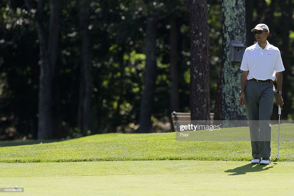President Barack Obama watches his putt on the first green at the Farm Neck Golf Club on August 9, 2014 in Oak Bluffs, Massachusetts. The Obama's are vacationing on the island for two weeks.