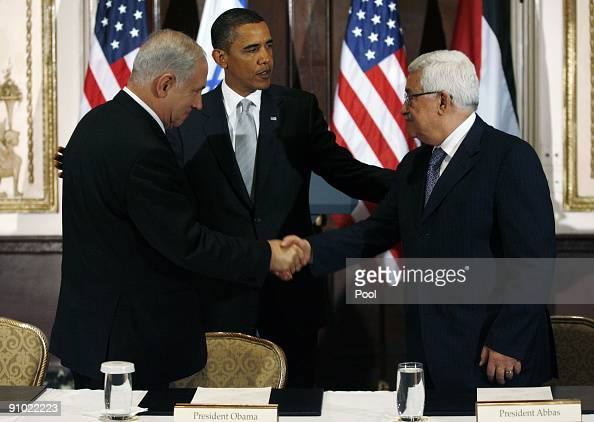 S President Barack Obama watches Israeli Prime Minister Benjamin Netanyahu and Palestinian President Mahmoud Abbas shake hands during a trilateral...