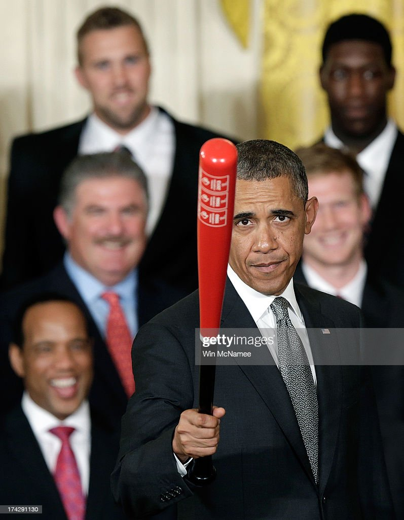 U.S. President <a gi-track='captionPersonalityLinkClicked' href=/galleries/search?phrase=Barack+Obama&family=editorial&specificpeople=203260 ng-click='$event.stopPropagation()'>Barack Obama</a> waves a Louisville Slugger baseball bat presented to him by the Louisville Cardinals, the 2013 NCAA Men's Basketball Champions, during an event in the East Room of the White House July 23, 2013 in Washington, DC. The Louisville Cardinals defeated the Michigan Wolverines in the championship game by a score of 82-76.