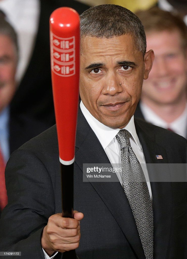 U.S. President Barack Obama waves a Louisville Slugger baseball bat presented to him by the Louisville Cardinals, the 2013 NCAA Men's Basketball Champions, during an event in the East Room of the White House July 23, 2013 in Washington, DC. The Louisville Cardinals defeated the Michigan Wolverines in the championship game by a score of 82-76.