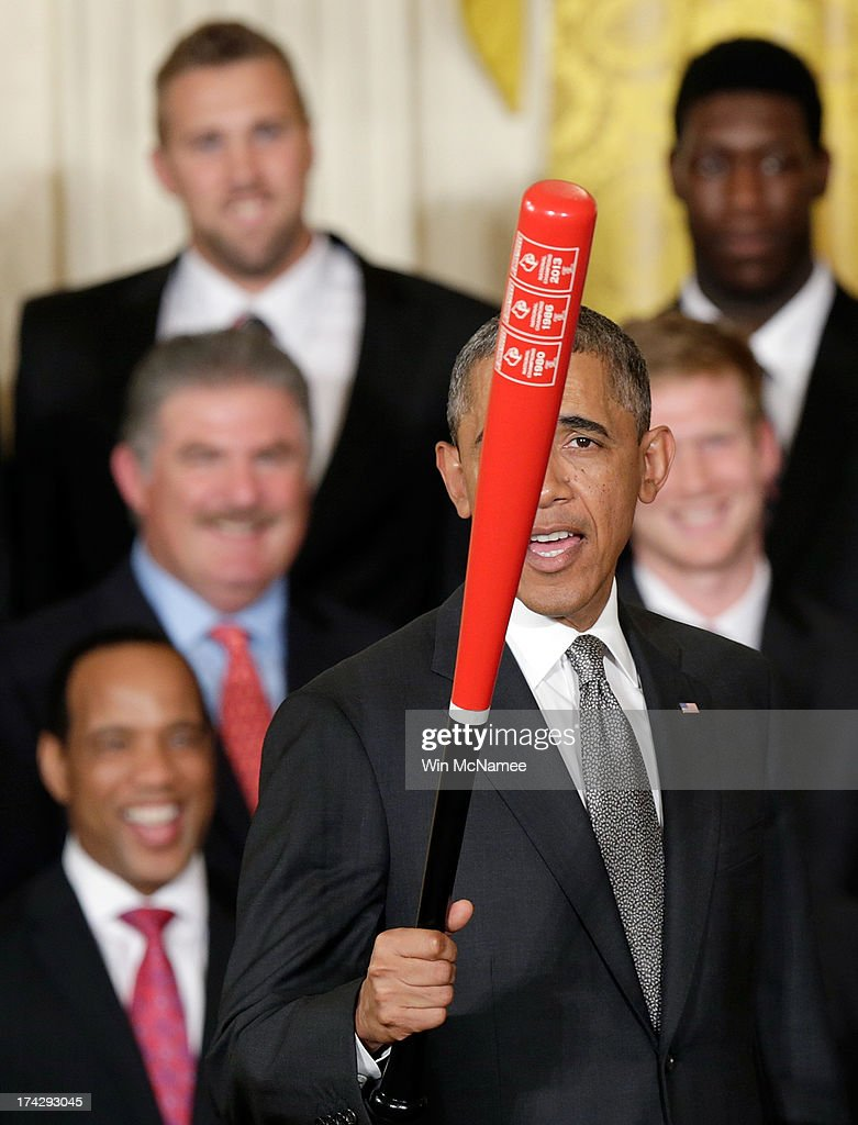 U.S. President Barack Obama waves a Louisville Slugger baseball bat presented to him by head coach Rick Pitino of the Louisville Cardinals, the 2013 NCAA Men's Basketball Champions, during an event in the East Room of the White House July 23, 2013 in Washington, DC. The Louisville Cardinals defeated the Michigan Wolverines in the championship game by a score of 82-76.