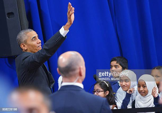 US President Barack Obama waves after greeting attendees in an overflow room at the Islamic Society of Baltimore in Windsor Mill Maryland on February...