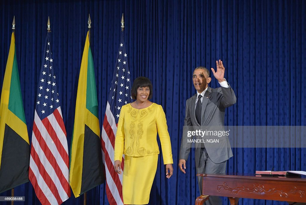 US President <a gi-track='captionPersonalityLinkClicked' href=/galleries/search?phrase=Barack+Obama&family=editorial&specificpeople=203260 ng-click='$event.stopPropagation()'>Barack Obama</a> waves after signing the guest book as Jamaica Prime Minister <a gi-track='captionPersonalityLinkClicked' href=/galleries/search?phrase=Portia+Simpson+Miller&family=editorial&specificpeople=4183773 ng-click='$event.stopPropagation()'>Portia Simpson Miller</a> (L) smiles at Jamaica House on April 9, 2015 in Kingston.