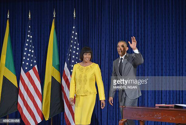 US President Barack Obama waves after signing the guest book as Jamaica Prime Minister Portia Simpson Miller smiles at Jamaica House on April 9 2015...