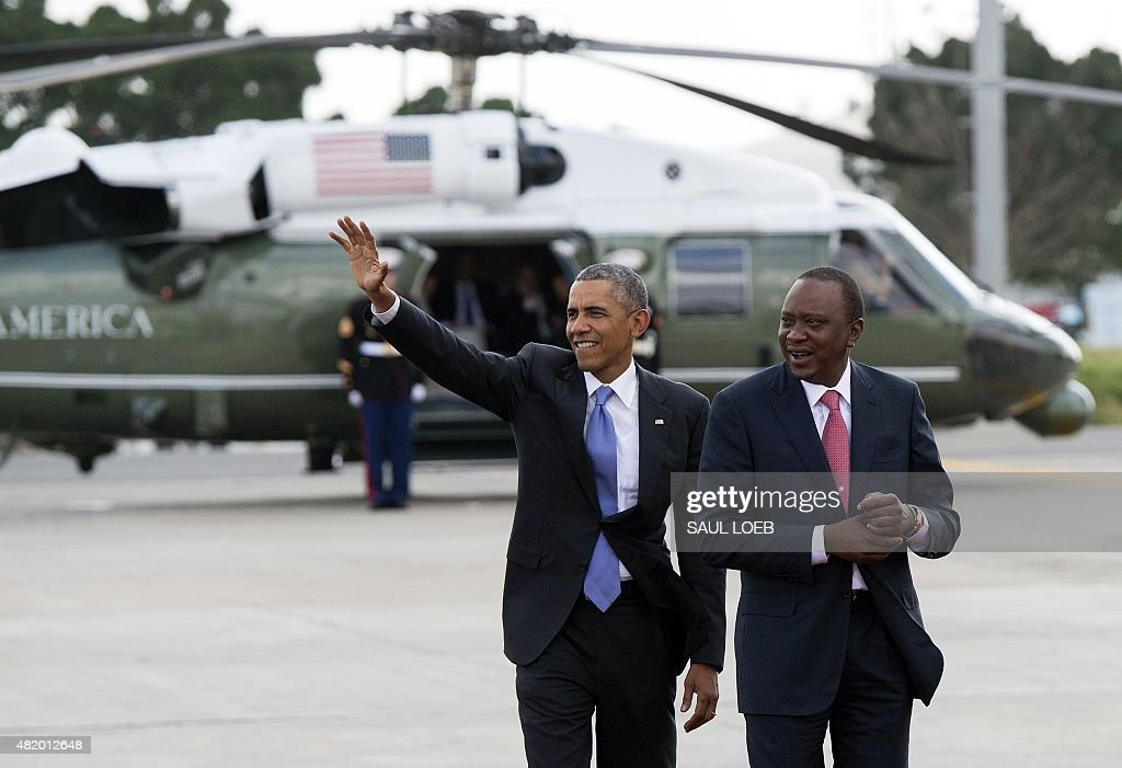 US President Barack Obama waves alongside his Kenyan counterpart Uhuru Kenyatta (R) before boarding Air Force One prior to his departure from Kenyatta International Airport in Nairobi on July 26, 2015. Obama urged Kenya to renounce corruption and tribalism, delivering a rousing speech at the end of a landmark visit to the East African nation and birthplace of his father.
