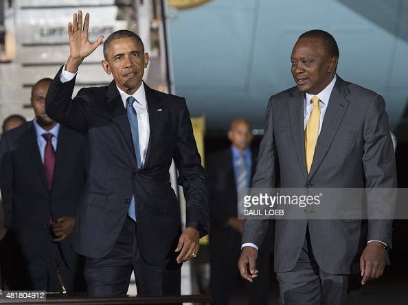 US President Barack Obama waves alongside Kenyan President Uhuru Kenyatta upon arrival on Air Force One at Kenyatta International Airport in Nairobi...