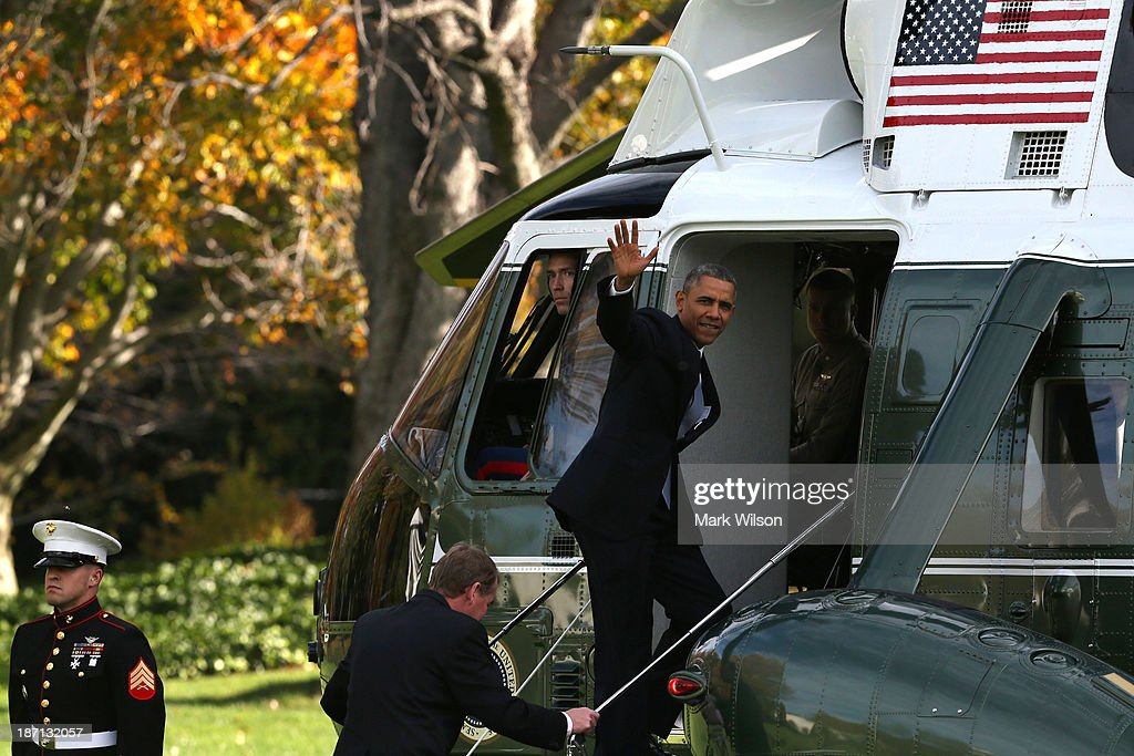 U.S. President <a gi-track='captionPersonalityLinkClicked' href=/galleries/search?phrase=Barack+Obama&family=editorial&specificpeople=203260 ng-click='$event.stopPropagation()'>Barack Obama</a> (R) waves as he and Sen. Michael Bennet (D-CO) board Marine One to depart the White House November 6, 2013 in Washington, DC. President Obama is traveling to Dallas, Texas to attend fundraisers and talk about the Affordable Health Care Act.