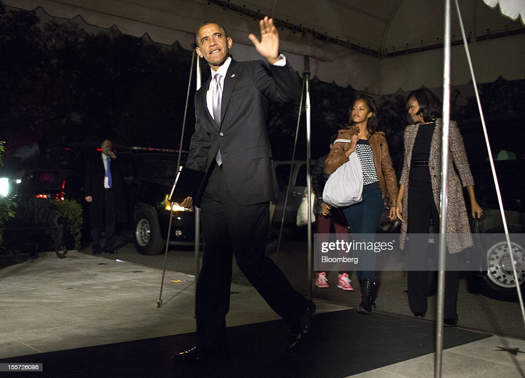 U.S. President Barack Obama waves as he arrives at the White House with First Lady Michelle Obama, right, and daughters Malia Obama, center, and Sasha Obama, unseen, in Washington, D.C., U.S., on Wednesday, Nov. 7, 2012. Obama, whose hope-and-change campaign promises yielded to grim economic realities in the White House, defied history to win re-election last night, as wary Americans seeing glimmers of a recovery handed him a second chance. Photographer: Joshua Roberts/Bloomberg via Getty Images