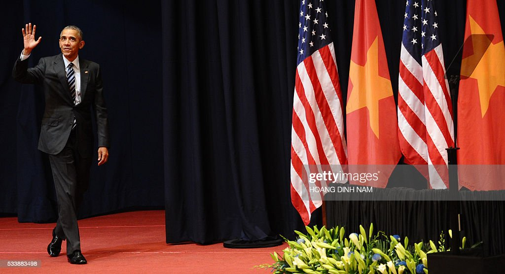 US President Barack Obama waves as he arrives to give a speech at the National Convention Center in Hanoi on May 24, 2016. Obama, currently on a visit to Vietnam, met with civil society leaders including some of the country's long-harassed critics on May 24. / AFP / POOL / HOANG