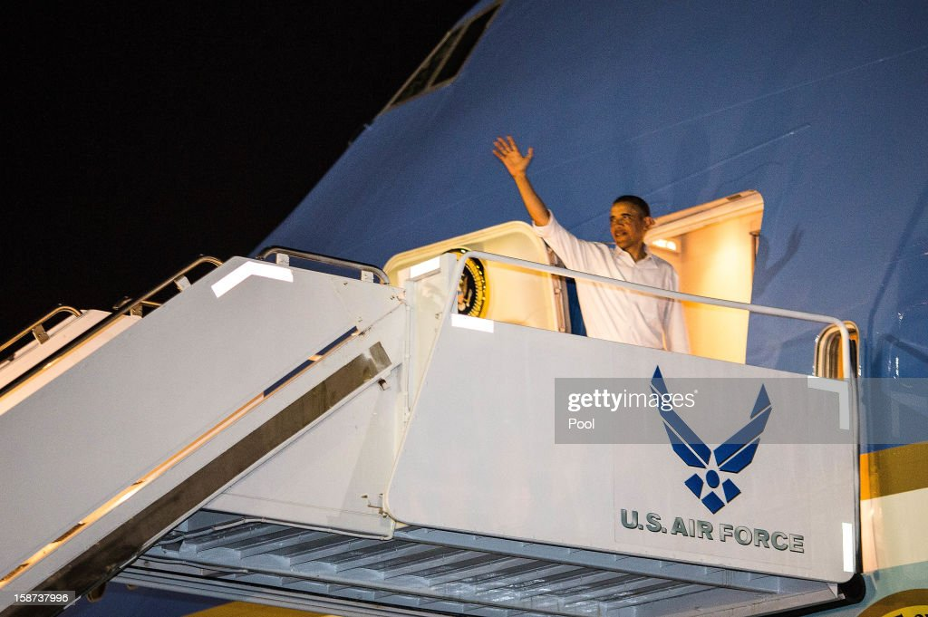US President <a gi-track='captionPersonalityLinkClicked' href=/galleries/search?phrase=Barack+Obama&family=editorial&specificpeople=203260 ng-click='$event.stopPropagation()'>Barack Obama</a> waves as he boards Air Force One at Joint Base Pearl Harbor-Hickam on December 26, 2012 in Honolulu, Hawaii. The president, who was spending a traditional Christmas holiday with his family in Hawaii, has been forced to cut his Christmas break short by the fiscal cliff crisis.