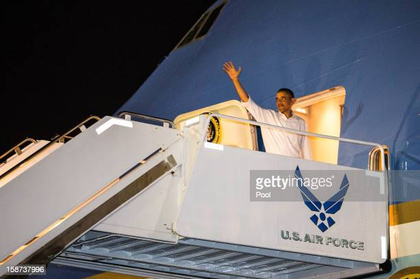 President Barack Obama waves as he boards Air Force One at Joint Base Pearl HarborHickam on December 26 2012 in Honolulu Hawaii The president who was...
