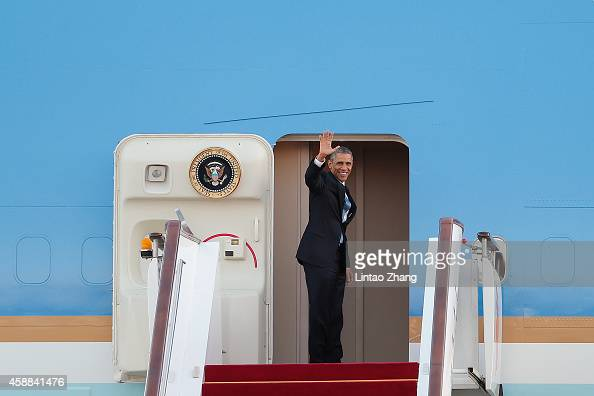 S President Barack Obama waves as he boards Air Force One at the Beijing Capital International Airport following a oneday state visit after attending...