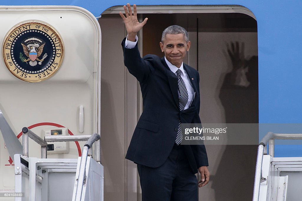 US President Barack Obama waves as he enters his plane 'Air Force One' prior to his departure on November 18, 2016 at the Tegel airport in Berlin, where the US President met the German Chancellor and other European leaders. US President Barack Obama's choice of Berlin as the stop for his European farewell tour has been interpreted by some observers as the passing of baton of the defence of liberal democracy to German Chancellor Angela Merkel. / AFP / CLEMENS