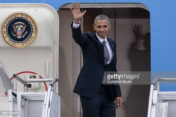 US President Barack Obama waves as he enters his plane 'Air Force One' prior to his departure on November 18 2016 at the Tegel airport in Berlin...