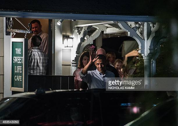 US President Barack Obama waves as he leaves the Sweet Life Cafe after having dinner at the restaurant with National Security Adviser Susan Rice...