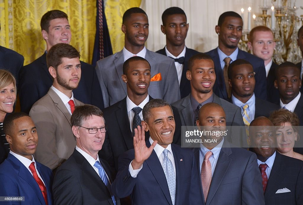 US President Barack Obama waves as he poses for a photo during an event in honor of the NCAA 2014 Champions, the UConn Huskies Mens and Womens Basketball teams in the East Room of the White House June 9, 2014 in Washington, DC. AFP PHOTO/Mandel NGAN