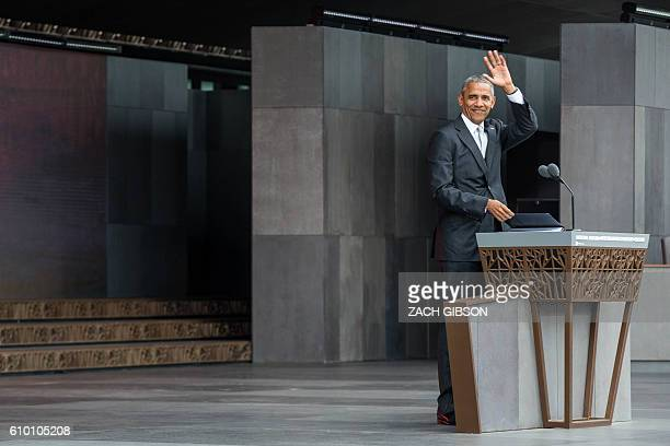 US President Barack Obama waves as he takes the podium before speaking during the opening ceremony for the Smithsonian National Museum of African...