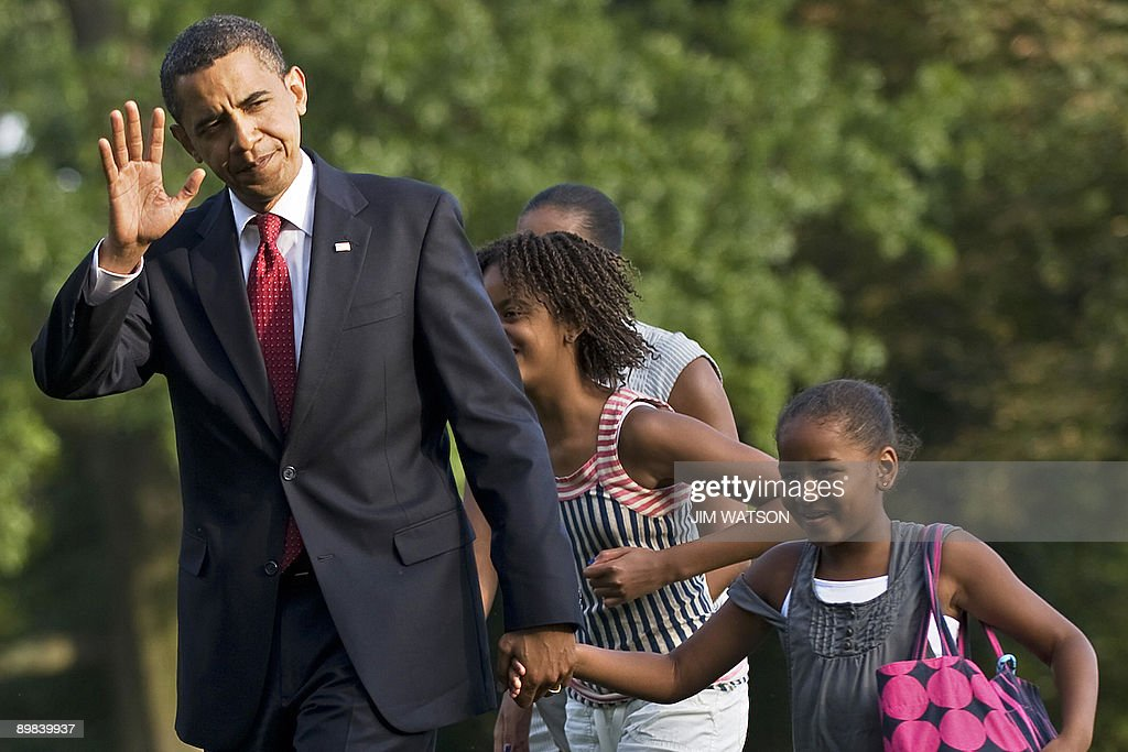 US President <a gi-track='captionPersonalityLinkClicked' href=/galleries/search?phrase=Barack+Obama&family=editorial&specificpeople=203260 ng-click='$event.stopPropagation()'>Barack Obama</a> (R) waves as he walks off Marine One with his daughters Malia (C) and Sasha (R), as well as First Lady <a gi-track='captionPersonalityLinkClicked' href=/galleries/search?phrase=Michelle+Obama&family=editorial&specificpeople=2528864 ng-click='$event.stopPropagation()'>Michelle Obama</a> (partially hidden) as they return the the White House in Washington on August 17, 2009. AFP PHOTO/Jim WATSON