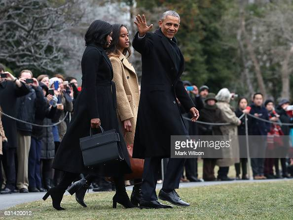 S President Barack Obama waves as he walks with first lady Michelle Obama and daughter Malia toward Marine One while departing from the White House...