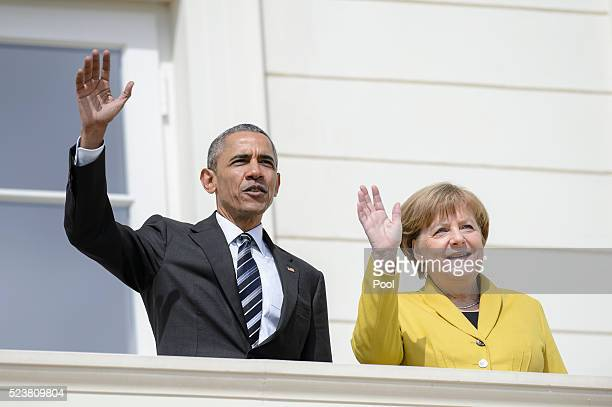 S President Barack Obama waves during a welcoming ceremony at Herrenhausen Palace accompanied by German Chancellor Angela Merkel on Obama's first day...