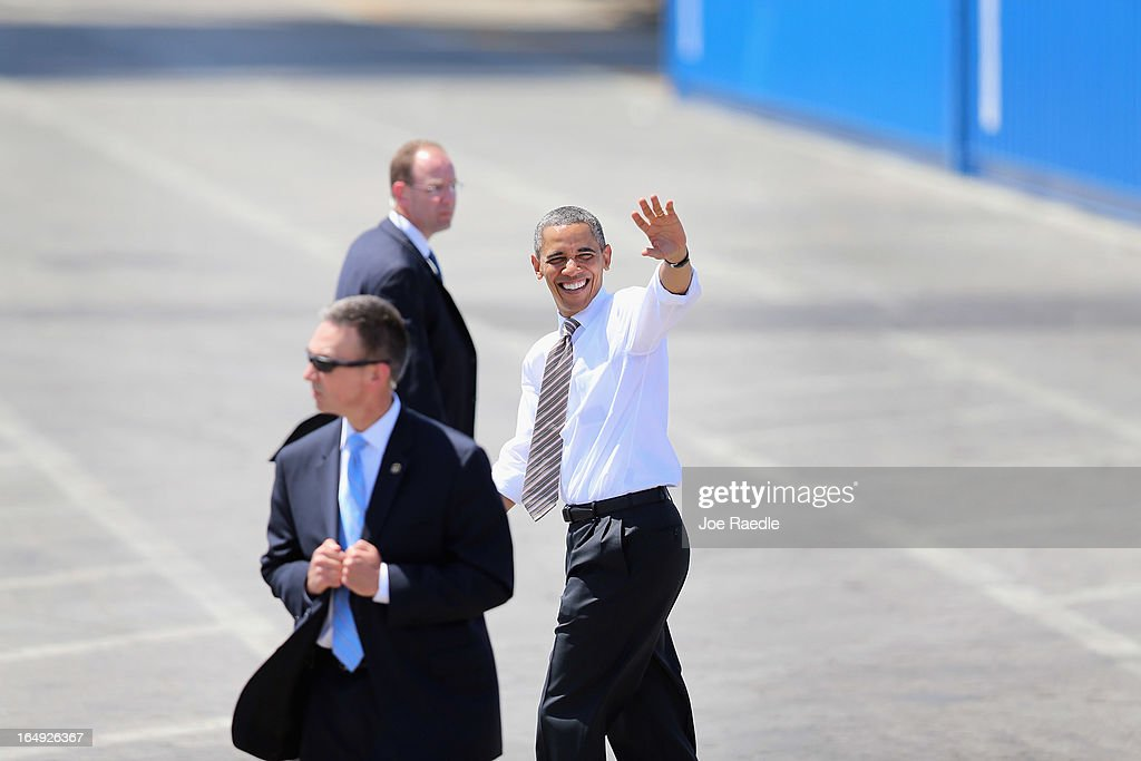 President <a gi-track='captionPersonalityLinkClicked' href=/galleries/search?phrase=Barack+Obama&family=editorial&specificpeople=203260 ng-click='$event.stopPropagation()'>Barack Obama</a> (R) waves during an event at PortMiami on March 29, 2013 in Miami, Florida. The president spoke about road and bridge construction during the event at the port in Miami, where he also toured a new tunnel project.