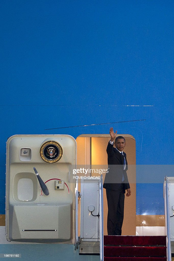 US President Barack Obama waves from Air Force One as he prepares to depart the Phnom Penh airport on November 20, 2012. US President Barack Obama on Tuesday defied Chinese protests and raised concerns at a summit about territorial disputes that have sent diplomatic and trade shockwaves across the region. AFP PHOTO / ROMEO GACAD
