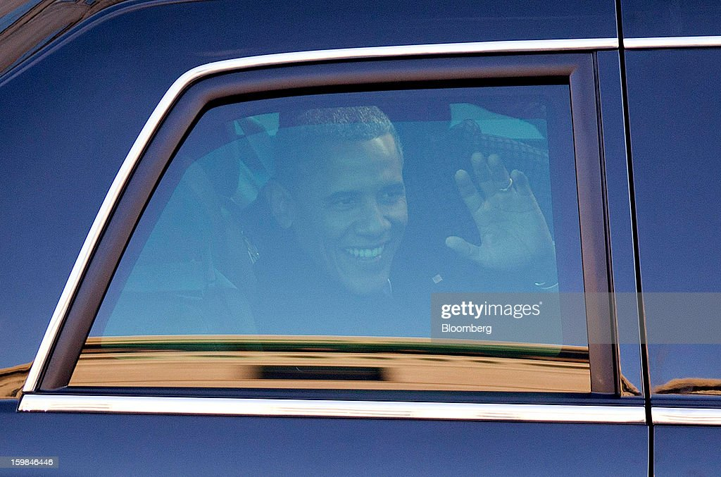 U.S. President Barack Obama waves from his limousine along the parade route during the inauguration in Washington, D.C., U.S., on Monday, Jan. 21, 2013. A crowd estimated by police to be as large as 700,000, including warmly dressed women with American flags stuck in their hair, a smattering of celebrities and many Republicans, gathered today to witness Obama take his second oath of office on the steps of the U.S. Capitol. Photographer: Andrew Harrer/Bloomberg via Getty Images