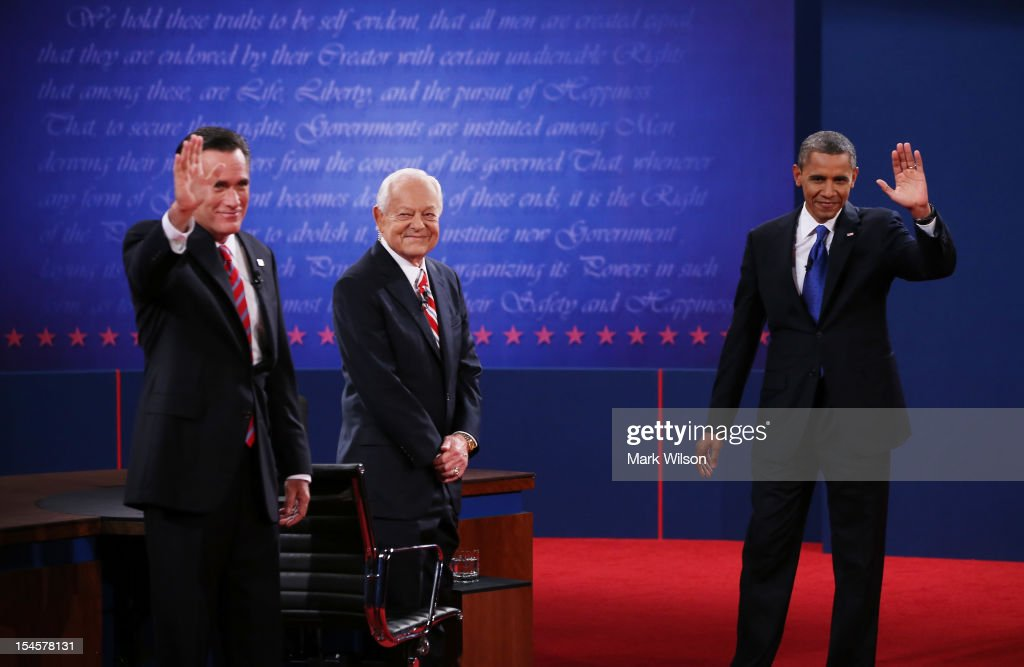 S President Barack Obama waves on stage with Republican presidential candidate Mitt Romney and moderator Bob Schieffer of CBS at the Keith C and...