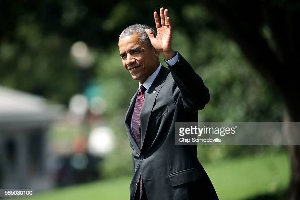 S President Barack Obama waves to guests as he crosses the South Lawn before boarding Marine One and departing the White House August 1 2016 in...