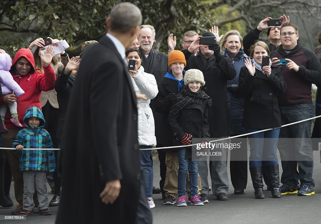 US President Barack Obama waves to guests as he walks to Marine One prior to departure from the South Lawn of the White House in Washington, DC, February 10, 2016. President Obama is en route to Springfield, Illinois where his White House journey began, to sell progress made in office and address one of the great failings of his presidency. / AFP / SAUL LOEB