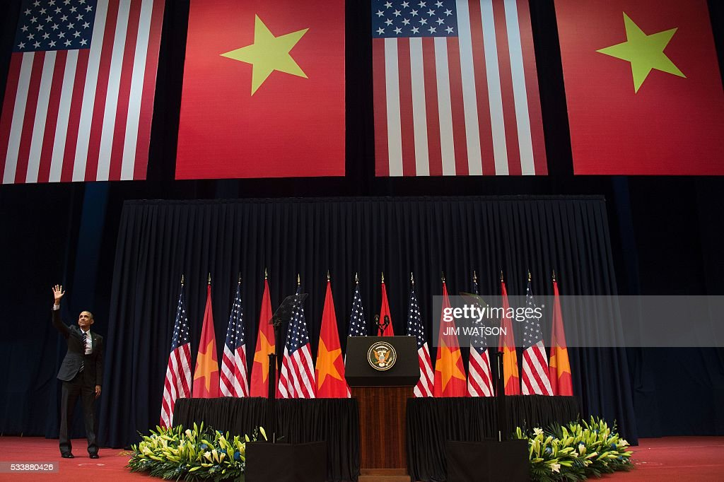 US President Barack Obama waves to the audience after delivering remarks at the National Convention Center in Hanoi on May 24, 2016. Obama, currently on a visit to Vietnam, met with civil society leaders including some of the country's long-harassed critics on May 24. / AFP / JIM