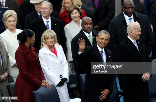 President Barack Obama waves to the crowd as Michelle Obama and Jill Biden stand by on the West Front of the US Capitol on January 20 2017 in...