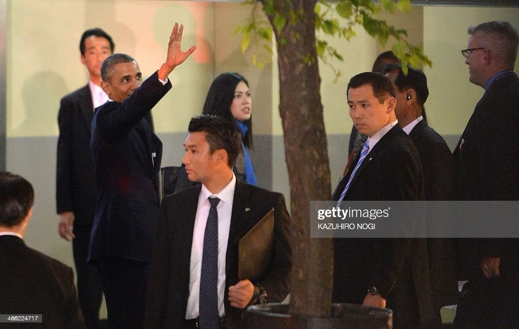 US President Barack Obama (L) waves upon his arrival at Sukiyabashi Jiro restaurant in Tokyo on April 23, 2014. Obama landed in Tokyo on April 23 to launch an Asian tour dedicated to reinvigorating his policy of 'rebalancing' US foreign policy towards a dynamic Asia. Sukiyabashi Jiro's less-than-plush surroundings notwithstanding, it is the proud possessor of three Michelin stars, and people flock to pay a minimum $300 for 20 pieces of sushi chosen by the 88-year-old patron, Jiro Ono. AFP PHOTO / KAZUHIRO NOGI
