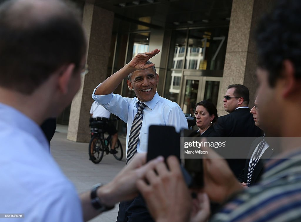 President Barack Obama waves while greeting people after picking up lunch at the Taylor Gourmet Deli, October 4, 2013 in Washington, DC. Democrats and Republicans are still at a stalemate on funding for the federal government as the shut down goes into the fourth day.