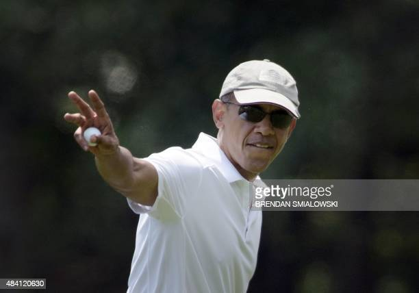 US President Barack Obama waves while leaving a green during a round of golf at Farm Neck Golf Club August 15 2015 in Oak Bluffs Massachusetts on...