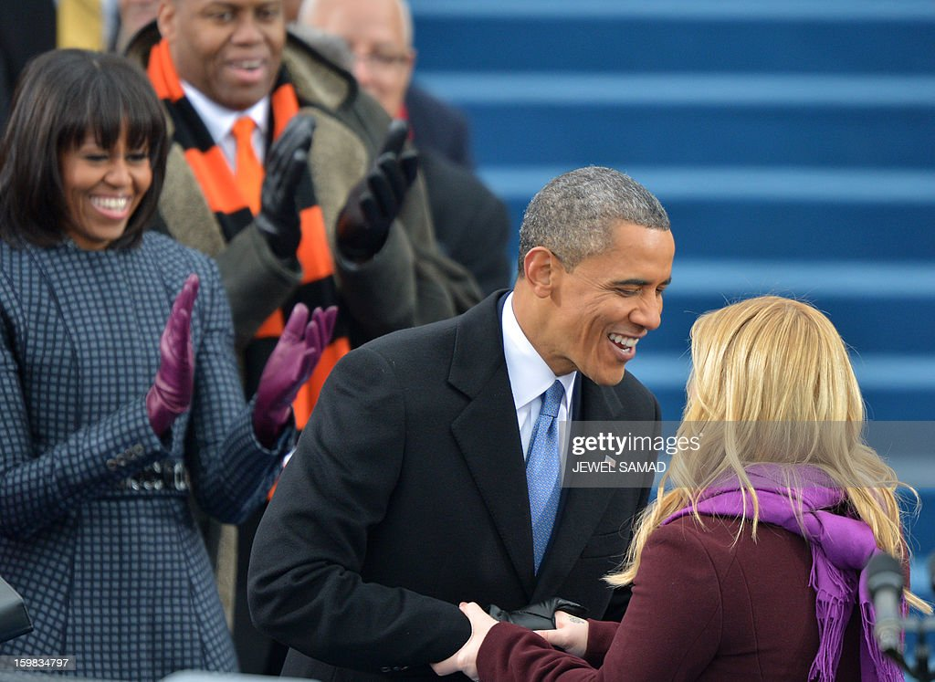 US President Barack Obama welcomes Kelly Clarkson as First Lady Michelle (L) applauds during the 57th Presidential Inauguration ceremonial swearing-in at the US Capitol on January 21, 2013 in Washington, DC. AFP PHOTO/Jewel Samad