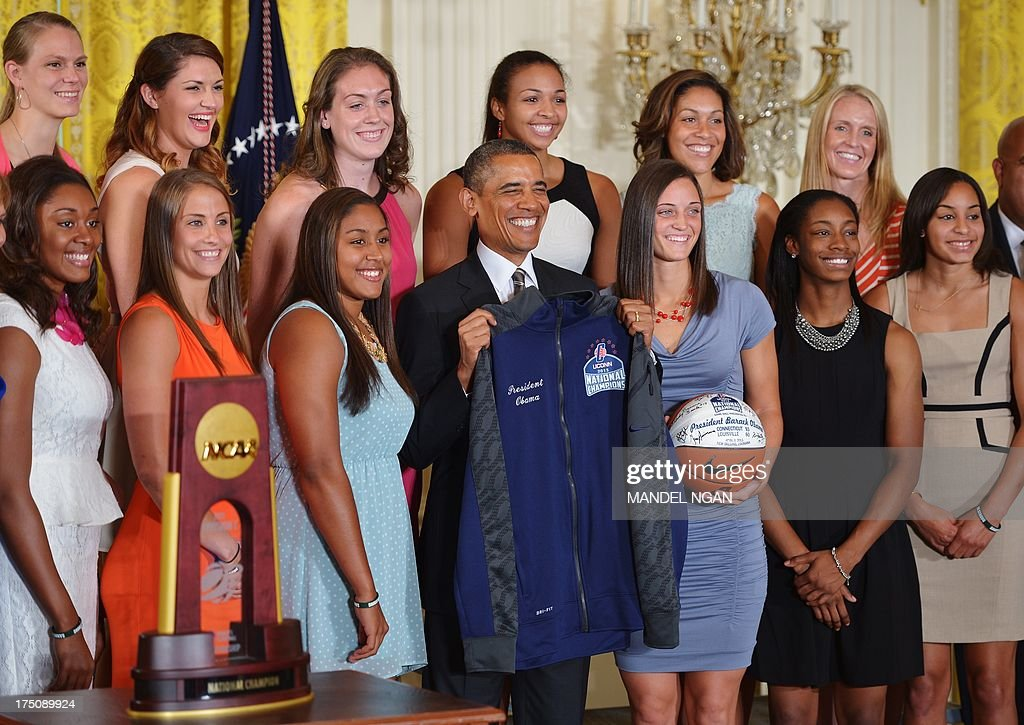 US President Barack Obama while posing for a photo after he received a jersey and basketball from the team during an event in honour of the 2013 NCAA Womens Basketball Champions, the University of Connecticut Huskies, in the East Room of the White House on July 31, 2013 in Washington, DC. AFP PHOTO/Mandel NGAN
