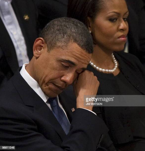 US President Barack Obama wipes away a tear as he sits next to First Lady Michelle Obama at the funeral service for Dr Dorothy Height at Washington...