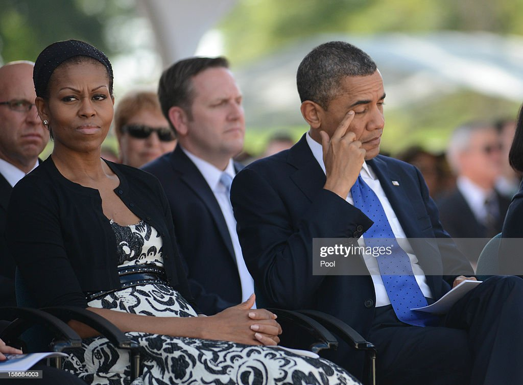U.S. President Barack Obama wipes his eyes sitting wtih First Lady Michelle Obama during the funeral services for the late Senator Daniel Inouye at the National Memorial Cemetery of the Pacific December 23, 2012 in Honolulu, Hawaii. Senator Inouye was a Medal of Honor recipient and a United States Senator since 1963.