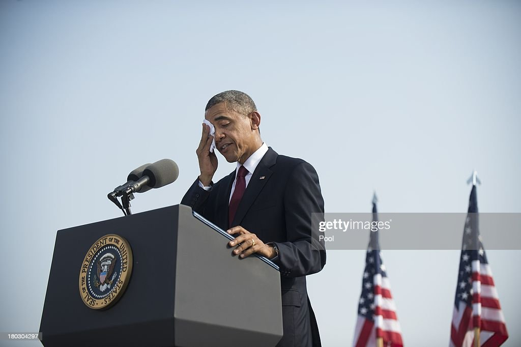 S. President <a gi-track='captionPersonalityLinkClicked' href=/galleries/search?phrase=Barack+Obama&family=editorial&specificpeople=203260 ng-click='$event.stopPropagation()'>Barack Obama</a> wipes his face while speaking during a ceremony in observance of the terrorist attacks of 9/11 at the Pentagon September 11, 2013 in Arlington, Virginia. Family members of the Pentagon attack victims and survivors of the attack gathered to hear from Obama and other leaders at the National 9/11 Pentagon Memorial near the place where terrorists drove a jetliner into the Department of Defense headquarters in 2001.