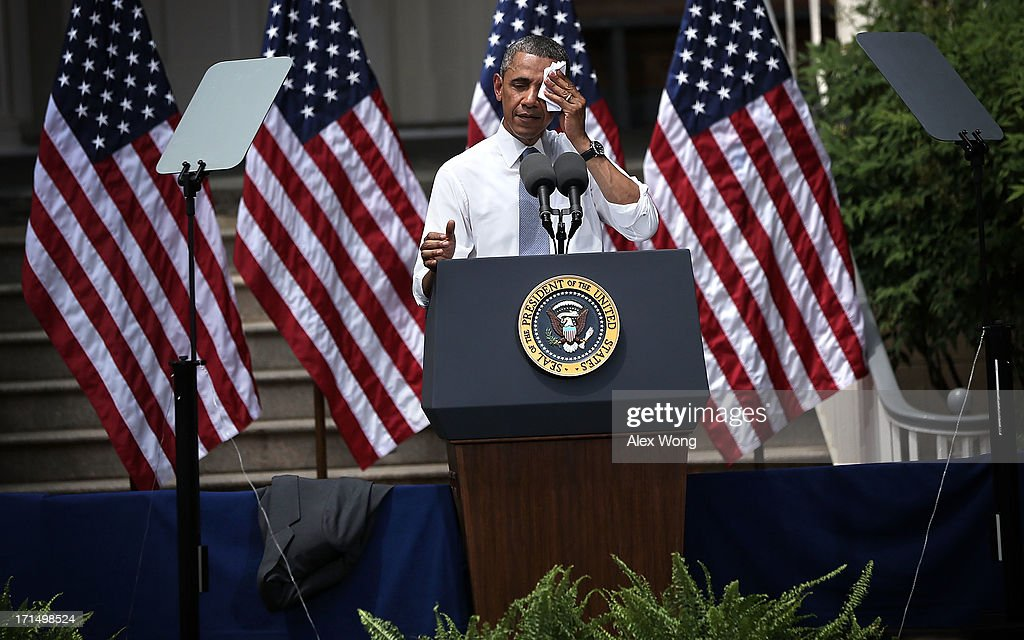 U.S. President Barack Obama wipes sweat off his face as he unveils his plan on climate change June 25, 2013 at Georgetown University in Washington, DC. President Obama laid out his plan to diminish carbon pollution and prepare the country for the impacts of climate change.