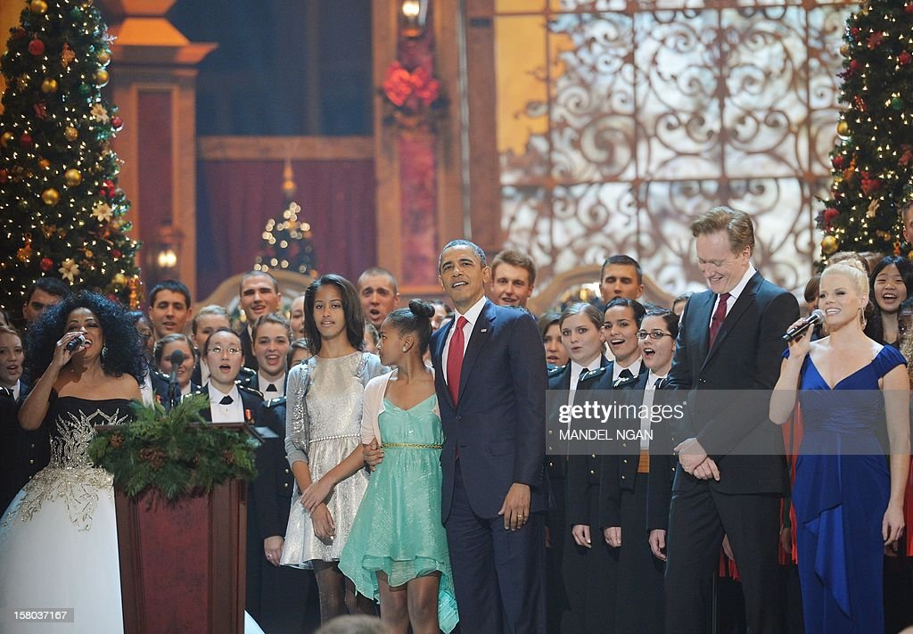 US President Barack Obama, with daughters Malia (3rd R) and Sasha (2nd R) and Diana Ross (L), host Conan O'Brien (2nd R) and Actress/singer Megan Hilty sing a Christmas carol during the taping of the 'Christmas in Washington' television special on December 9, 2012 at the Building Museum in Washington, DC. AFP PHOTO/Mandel NGAN