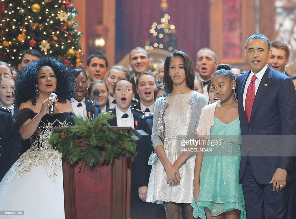 US President Barack Obama, with daughters Malia (3rd R) and Sasha (2nd R) sing a Christmas carol with Diana Ross (L) during the taping of the 'Christmas in Washington' television special on December 9, 2012 at the Building Museum in Washington, DC. AFP PHOTO/Mandel NGAN