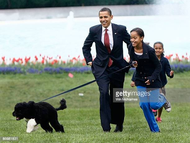 S President Barack Obama with his daughters Malia and Sasha walk the family's new Portuguese water dog Bo during the dog's introduction to the White...