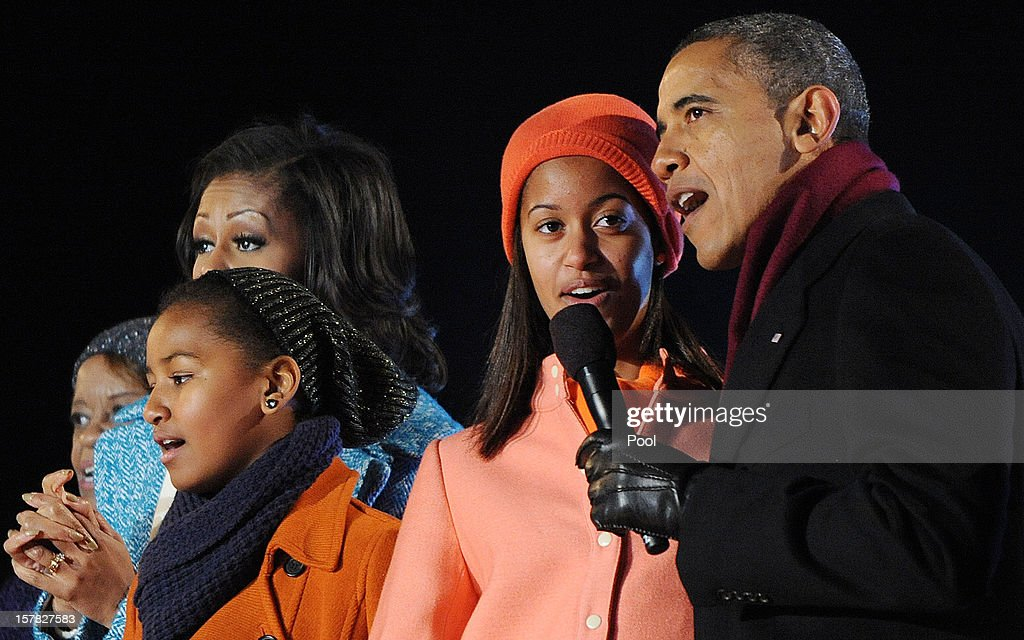U.S. President Barack Obama (R) with his wife first lady Michelle Obama (2nd L) and their daughters Malia (2nd R) and Sasha Obama (C), and mother-in-law Marion Robinson (L) sing during the 90th National Christmas Tree Lighting Ceremony on the Ellipse behind the White House on December 6, 2012 in Washington, DC. This year is the 90th annual National Christmas Tree Lighting Ceremony.