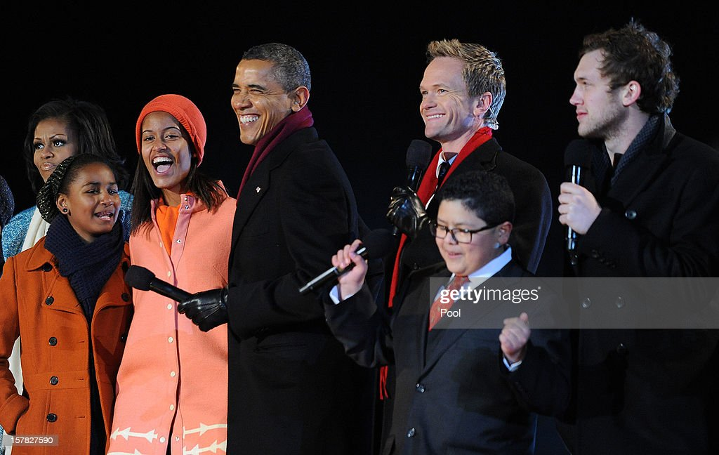 U.S. President Barack Obama (C) with his wife first lady Michelle Obama and their daughters Malia and Sasha Obama, and mother-in-law Marion Robinson (L) sing on stage with actor Neil Patrick Harris (3rd R), Rico Rodriguez (2nd R) , actor on Modern Family, and Phillip Phillips (R), winner of 'American Idol' Season 11, during the 90th National Christmas Tree Lighting Ceremony on the Ellipse behind the White House on December 6, 2012 in Washington, DC. This year is the 90th annual National Christmas Tree Lighting Ceremony.