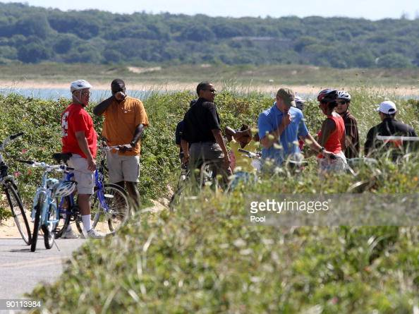 President Barack Obama with wife Michelle Obama brotherinlaw Konrad Ng and friend Eric Whitaker ride their bikes August 27 2009 in Aquinnah Martha's...