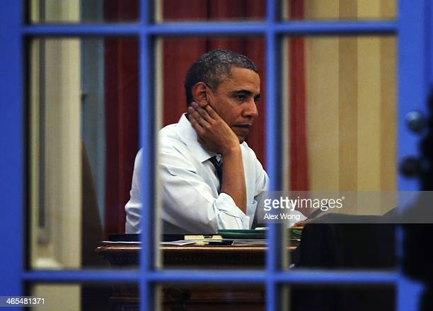 S President Barack Obama works on a draft of his State of the Union address in the Oval Office January 27 2014 at the White House in Washington DC...