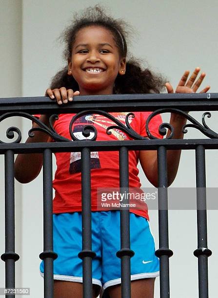 S President Barack Obama's daughter Sasha waves to him from the Truman Balcony after he arrived on the south lawn of the White House via Marine One...