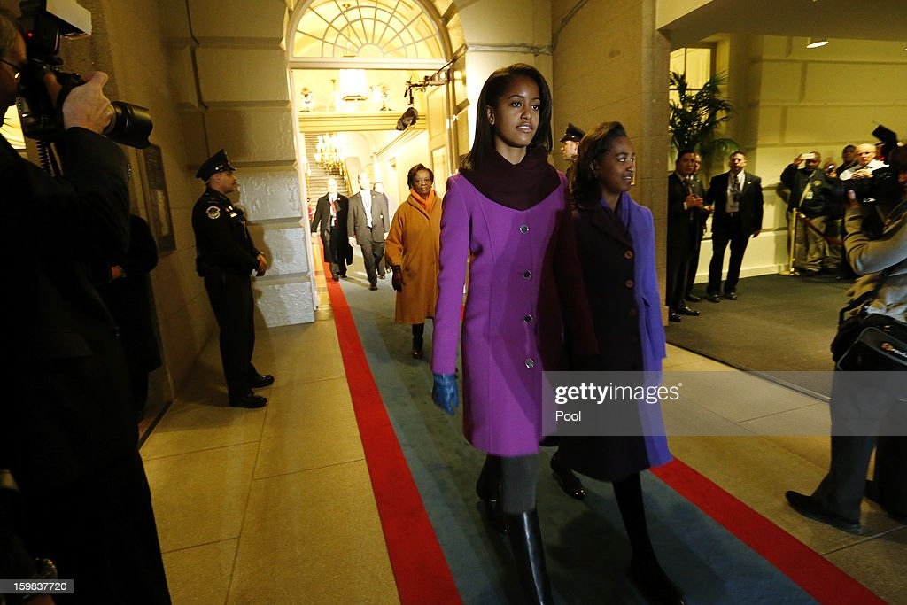 U.S. President Barack Obama's daughters Malia Obama (L) and Sasha Obama (R) are escorted through the corridor to the west door of the U.S. Capitol to begin swearing-in ceremonies on January 21, 2013 in Washington, DC. U.S. President Barack Obama will be ceremonially sworn in for his second term today.